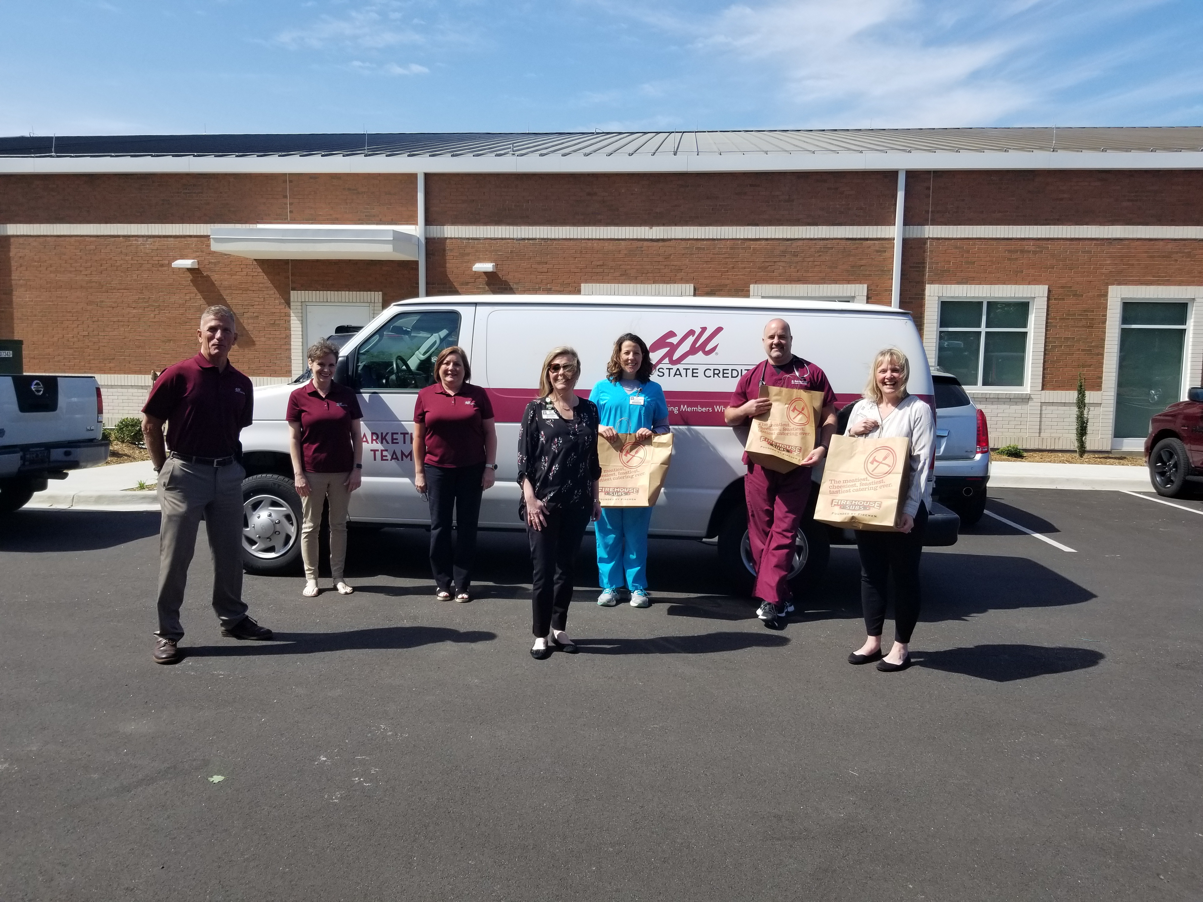 SCU president Jim Kinard poses for a photo with two SCU staff members and 4 LMC employees in a rough semi-circle in the hospital parking lot in front of a white SCU van, with the LMC employees holding large paper bags from Firehouse Subs.