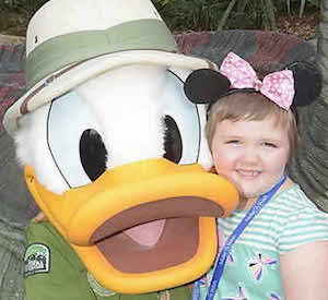 A smiling child poses with Daffy Duck.