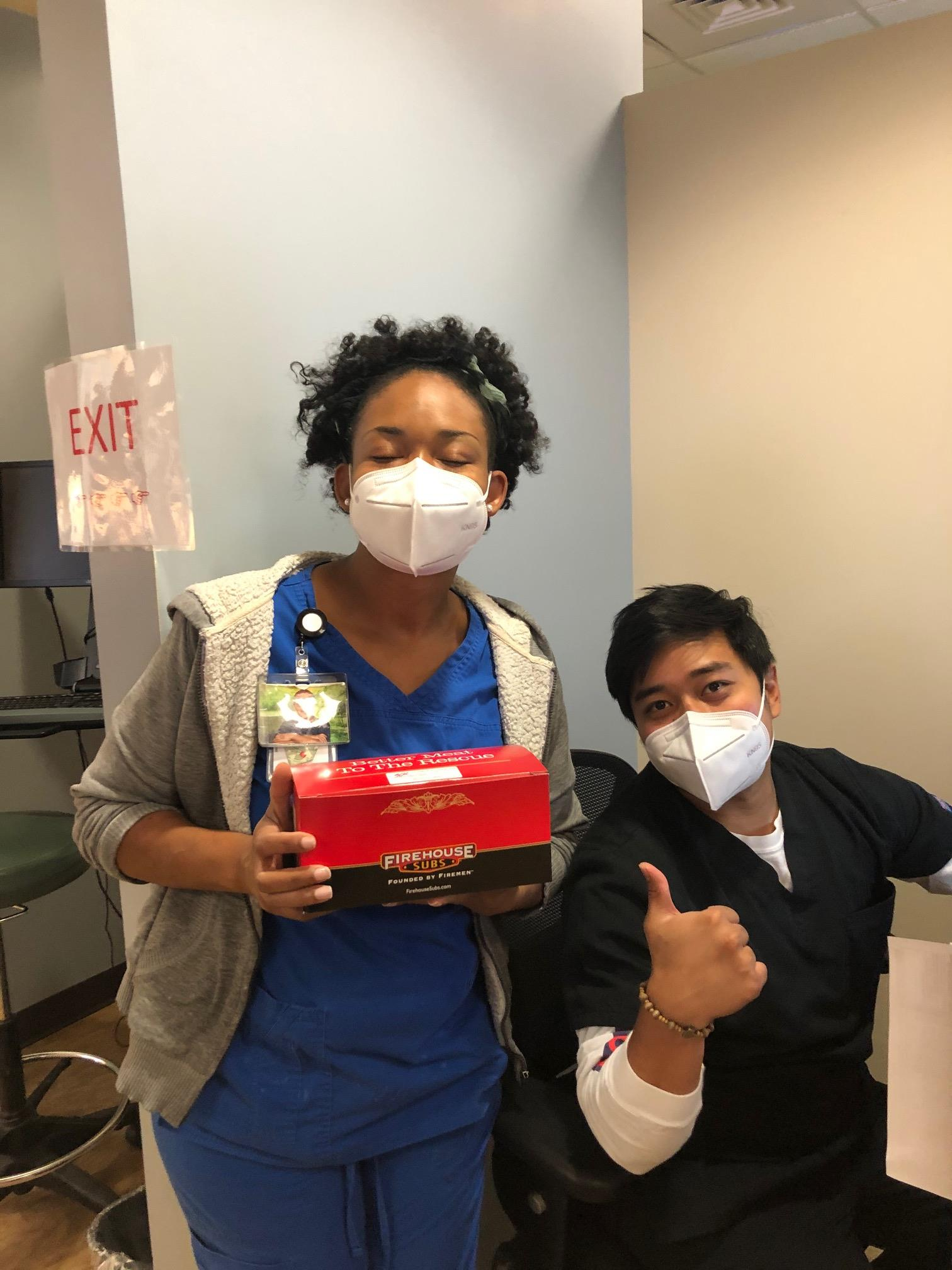 In a hallway at Palmetto Primary Urgent Care, two employees next to an exit sign wear face masks, one in blue scrubs smiling as she stands holding a box from Firehouse Subs and the other in black scrubs, seated, giving a thumbs up.